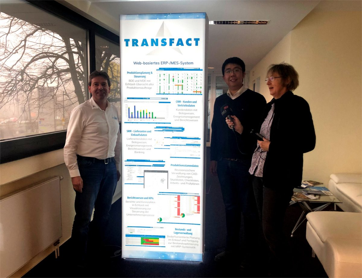 Anette Jaciuk in front of a Transfact Poster with Heiko Martin and Yang Yang